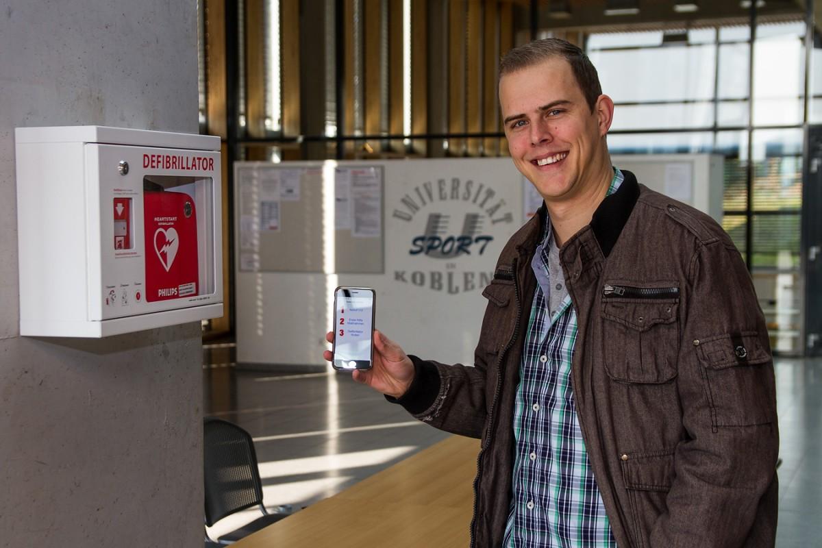 """Wie geht Erste Hilfe und wo finde ich einen Defibrillator? Diese Fragen beantwortet die App """"Defi-Now!"""". Marco Krause, wissenschaftlicher Mitarbeiter am Koblenzer Institut für Wirtschafts- und Verwaltungsinformatik, hat die Erste-Hilfe-App mitentwickelt. Auch in der Turnhalle am Campus Koblenz ist ein Laien-Defibrillator angebracht. Fotos: Marius Adam"""