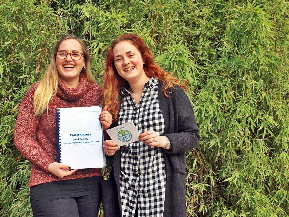 Ines Scheuffele (l.) und Nina Charlotte Kelle halten stolz ihre Projektarbeit über das von ihnen betreute Mentoringprogramm für Ärzte in den Händen. Foto: Esther Guretzke