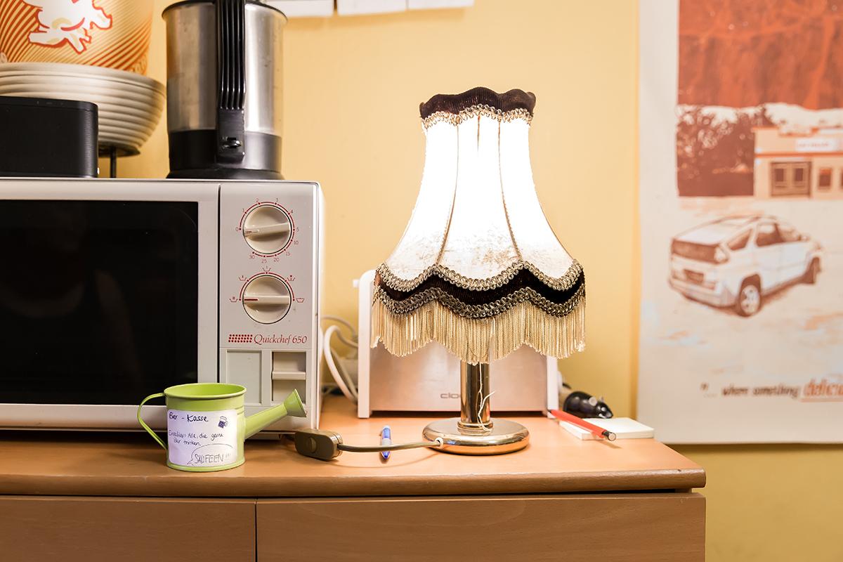 Die Bierkasse in Form einer kleinen Gießkanne und die alte Nachttischlampe in der Küche. Foto: Teresa Schardt